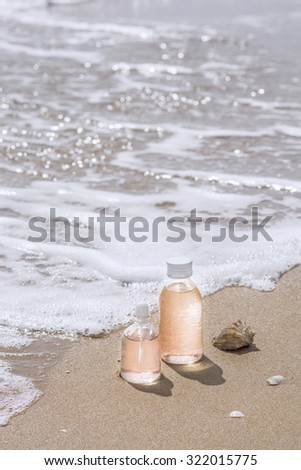 Bottles with oil essence and shell in the sea waves. Spa and wellness setting. fragrance, aromatherapy, relax and treatment therapy. Manicure and Pedicure set. Copy space.  Selective focus. Close up. - stock photo