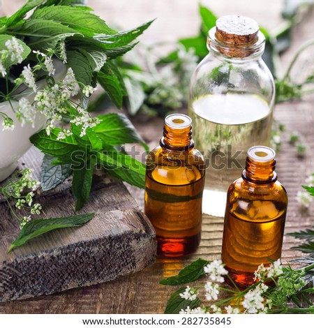 Bottles with organic essential aroma oil with mint  on aged wooden background. Selective focus. Square image. - stock photo