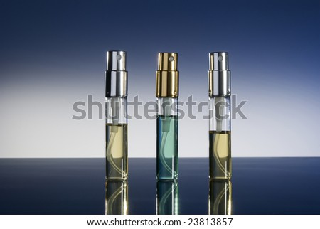bottles with perfume isolated on gradient background - stock photo