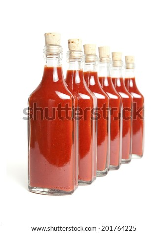 Bottles with red hot chili sauce in a row on a white background. - stock photo