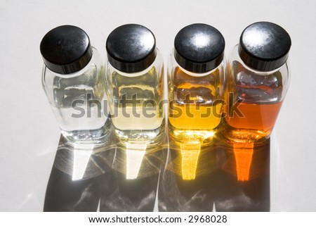Bottles with samples of different base oils against sunlight - stock photo