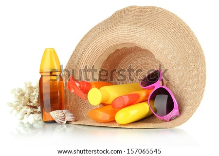 Bottles with suntan cream and sunglasses in hat isolated on white - stock photo