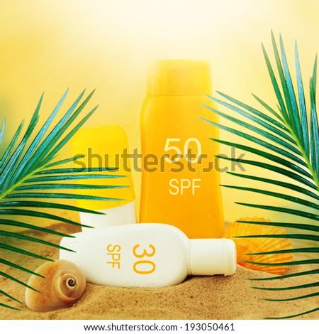 Bottles with suntan cream on the sand. - stock photo