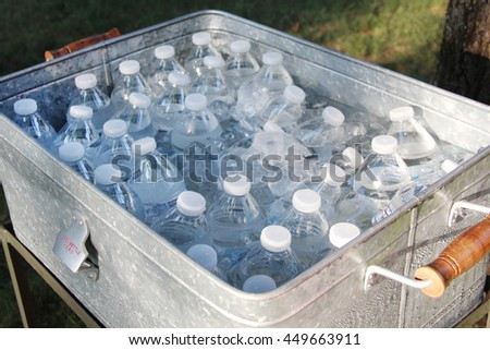 Bottles with water in a large cart filled with ice - stock photo