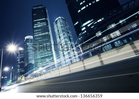 Bottom angle shooting highway car light trails of modern urban buildings