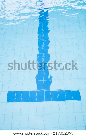 Bottom lane line at end of swimming pool with T-shape slightly distorted by water - stock photo