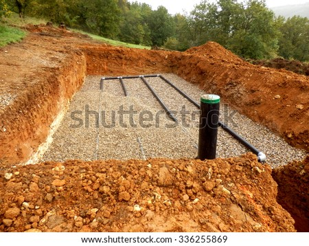 Bottom layer of pipework laid on gravel in the construction of a sand and gravel drainage system - stock photo