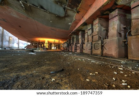 Bottom of the ship supported on large blocks in dry dock - stock photo