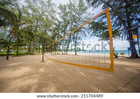 Bottom of yellow volleyball net on beach among palm trees - stock photo