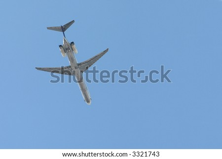 Bottom side of a passenger jet flying over in a blue sky. - stock photo