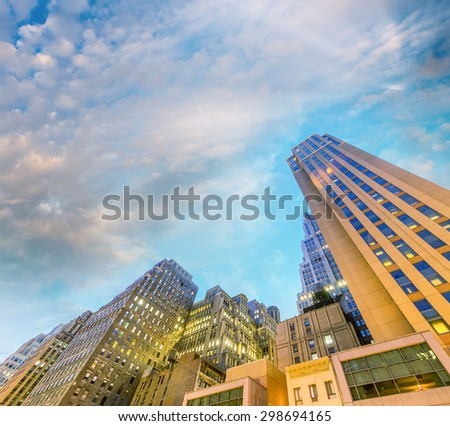 Bottom up amazing view of Manhattan skyscrapers at night. Streets of New York City. - stock photo