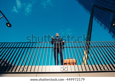 Bottom up perspective of middle-age contemporary businessman leaning on a handrail holding smart phone - work, business, technology concept - stock photo