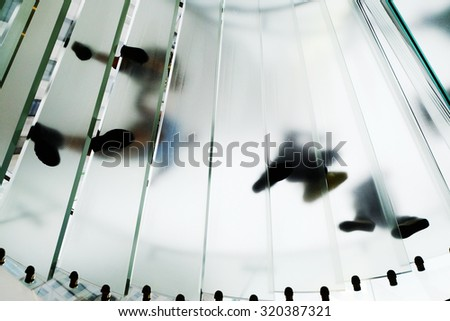 Bottom Up view of walking on spiral staircase. Walking people at glass stairs.  - stock photo