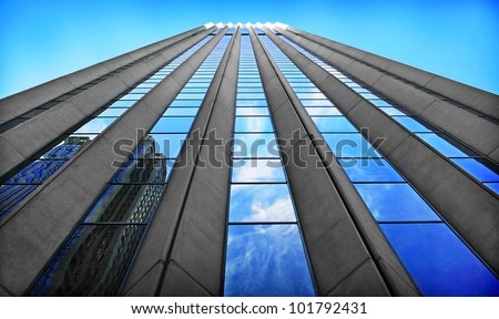 Bottom view of a skyscraper with blue sky - stock photo