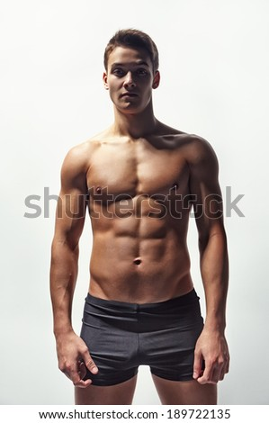 Bottom view of a young sexy muscular man in underwear on a white background