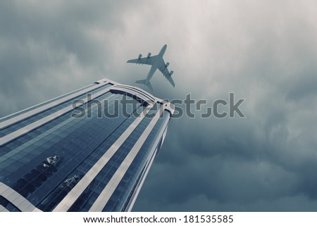 Bottom view of airplane flying above skyscrapers