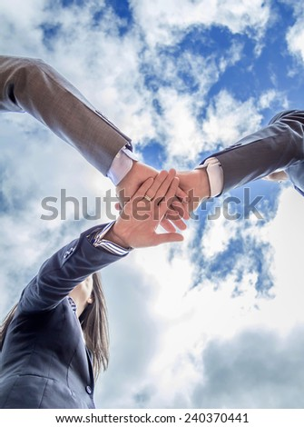 Bottom view of business team showing unity with hands together over blue sky background - stock photo