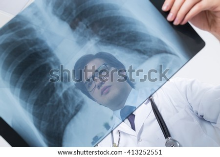 Bottom view of caucasian doctor's face behind chest x-ray - stock photo