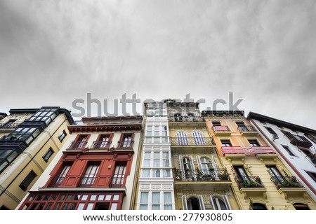 Bottom view of colorful houses in Bilbao with athletic team flags - stock photo