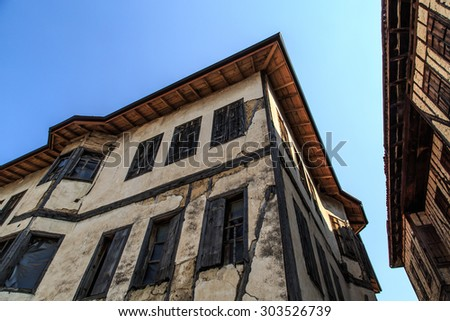 Bottom view of historical old and abandoned wooden and stone house of Yoruk Village in Safranbolu, Karabuk, on blue sky background. - stock photo