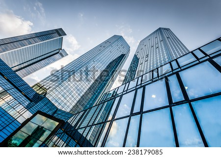 Bottom view of modern skyscrapers in business district against blue sky - stock photo