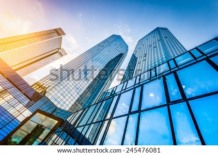 Bottom view of modern skyscrapers in business district at sunset with lens flare filter effect - stock photo