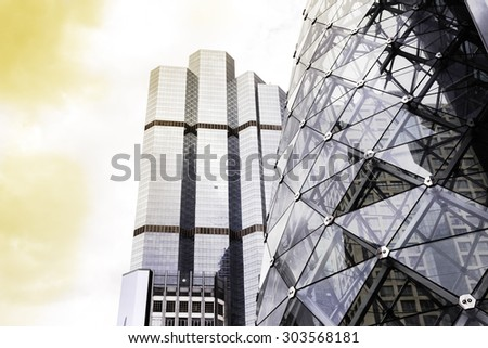 Bottom view of modern skyscrapers in business district in evening light at sunset with lens flare filter effect - stock photo