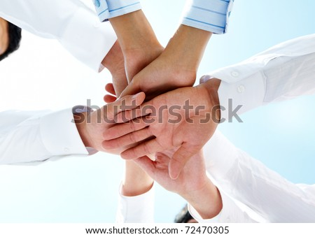 Bottom view of people hands holding together on a sky background - stock photo