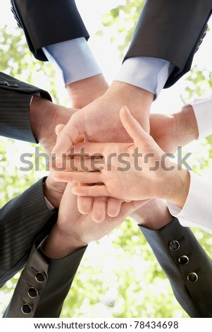 Bottom view of people hands holding together on background of green foliage - stock photo