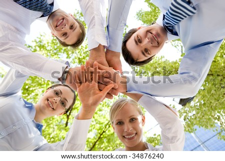 Bottom view of people making pile of hands on background of green foliage - stock photo