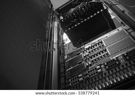 Bottom view of rack server against neon light in datacenter with dept of field in black & white tone - stock photo