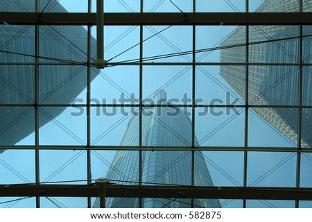 Bottom view on skyscrapers through the glass roof - stock photo