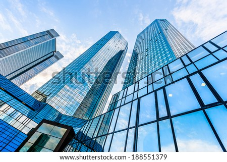 Bottom wide angle view of modern skyscrapers in business district with blue sky and clouds - stock photo