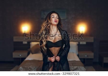 Boudoir photo of sexy girl wearing stylish black lingerie underwear posing in the bedroom - stock photo