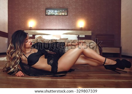 Boudoir photo of sexy girl wearing stylish black lingerie underwear posing in the bedroom - stock photo