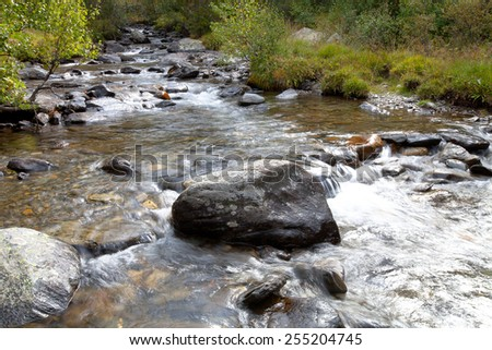 Boulder in the turbulent flow of a mountain river. - stock photo