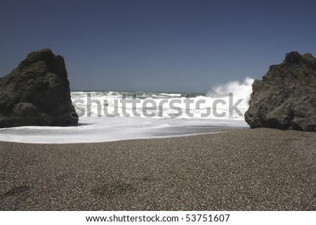 Boulders and footprints on California coast with waves rolling in onto a pebble beach with dark blue sky in the background. - stock photo