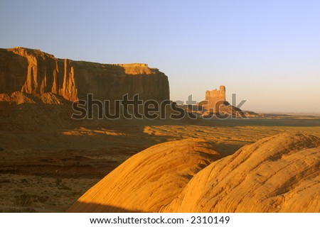 Boulders and mesas lit by the setting sun in Monument Valley, Navajo Nation. - stock photo