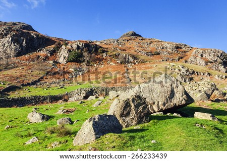 Boulders before the Langdale Pikes. A pile of fallen boulders lie in a field behind which the magnificent Langdale Pikes are lit by the autumn sun. - stock photo