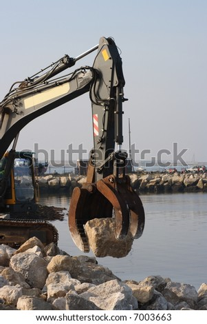 Boulders being positioned to strengthen a coastal sea wall, defense against rising sea levels due to global warming. - stock photo
