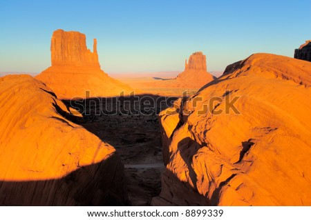 Boulders framing Mittens in Monument Valley, Navajo Nation are lit by setting sun - stock photo