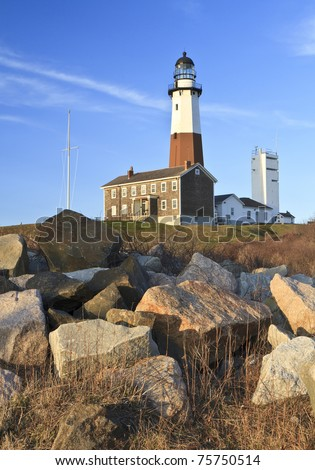 Boulders lie below Montauk Lighthouse on a clear day at the Eastern tip of Long Island, NY - stock photo