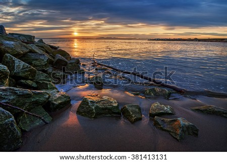 Boulders on the beach, glimpse of the orange sunset through the gray clouds - stock photo