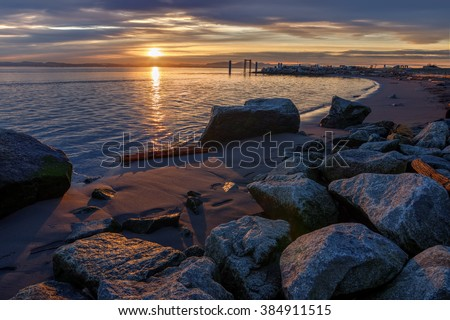 Boulders on the sandy beach, ripples on the sea, low sunset through the clouds - stock photo