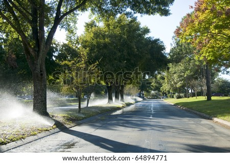 Boulevard with irrigation activated and overspraying the street - stock photo