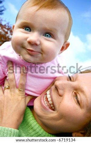 Bouncing baby girl lifted up on her mom's shoulder, an outdoor setting.
