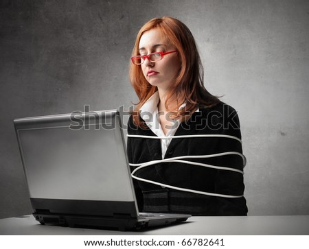 Bound businesswoman sitting in front of a laptop - stock photo