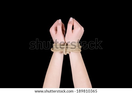 Bound hands isolated on black background. - stock photo