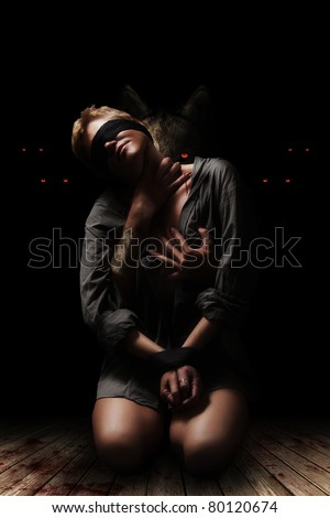 Bound woman in the arms of a werewolf - stock photo