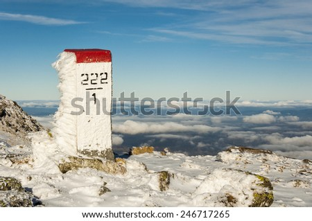 Boundary marker  in the background valley covered with clouds  - stock photo